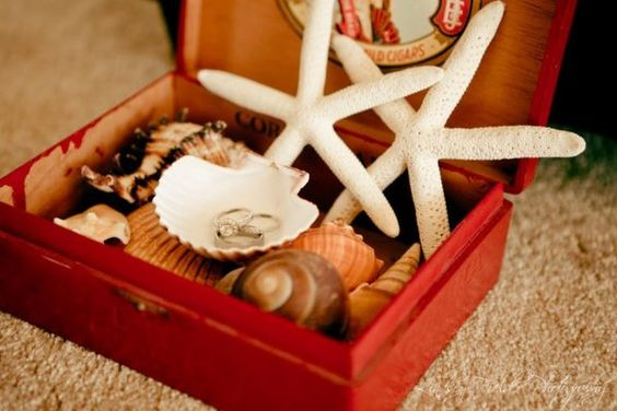 DIY - Vintage cigar box, painted to your wedding color. Purchase seashells and starfish - arrange accordingly (use glue gun as needed). Turn one sea shell upside down and glue to base shells - this shell will be the actual ring holder.