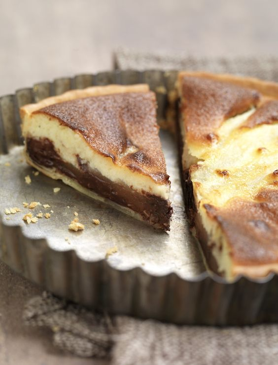 Préchauffez votre four Th.7/8 (220°C). Faites fondre le chocolat cassé en morceaux au bain-marie. Déroulez la pâte dans un moule à tarte en conservant la feuille de cuisson. Piquez la pâte avec une fourchette. Nappez le fond de tarte de chocolat fondu. Lavez et pelez les poires puis coupez-les en lamelles. Déposez-les sur le chocolat. Dans un saladier, mélangez la crème, l'œuf, la poudre d'amandes et le sucre. Versez la préparation sur les poires.