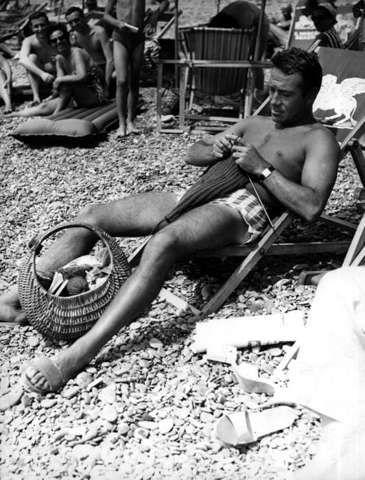 Ugo Tognazzi ( Italian film, TV, and theatre actor, director, and screenwriter) knitting on the beach: