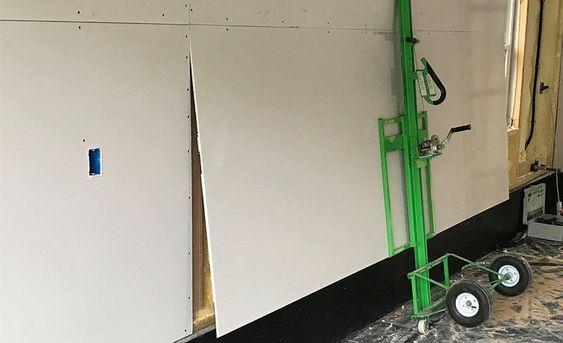 Еще больше гипсокартона кладут на стену с помощью подъемника для гипсокартона.