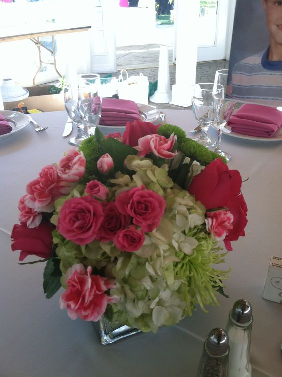 Hot pink and green centerpiece with green hydrangea, pink carnations, hot pink spray roses, green kermit buttons, and green spider mums.