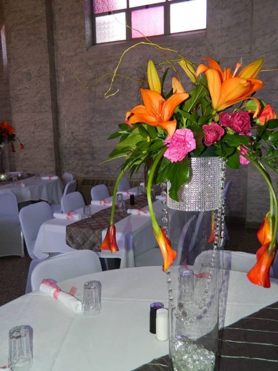 Floral topper on blinded out vase using orange lilies, fuchsia roses and dianthus and hanging miniature calla lilies.