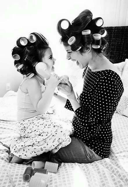 Mother and child laughing with curlers in hair.