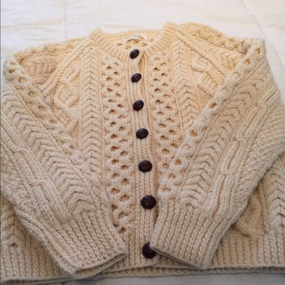 Cable Hand-Knitted Bone Sweater This Cable Knit hand crafted sweater is bone with brown buttons and has 2 pockets in total. Size is medium and It is 100% made of wool so it is very warm. The detail is impressive and lovely. Made in the Aran Islands. An Pucan Sweaters
