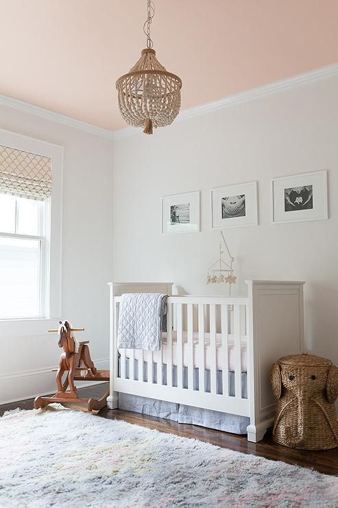 Blue and pink nursery features a pink cieling accented with a white beaded chandelier, PB Kids Dahlia Chandelier, illuminating a white crib, Fiona Crib, dressed in blue crib bedding next to a wicker elephant hamper alongside a West Elm Ashik Wool Rug - Multi.