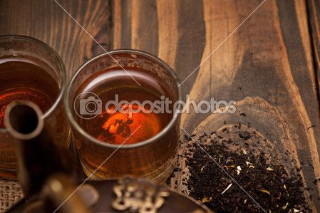 Glass of hot tea and leaves on dark wooden background — Stock Photo © irinabort #52967447