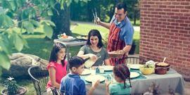 Una familia disfrutando de una comida juntos en el patio de su casa