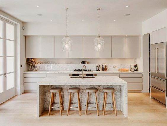A gray-tone marble island and matching countertops is the ideal serene match for overcast cabinetry and light wooden flooring.: