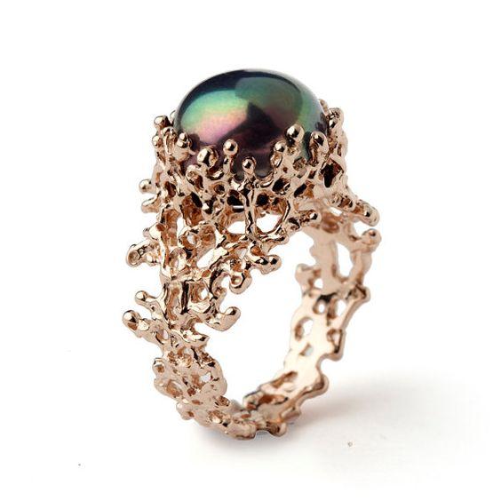 Um anel de noivado completamente diferente, que simula um coral em seu aro segurando uma pérola negra.
