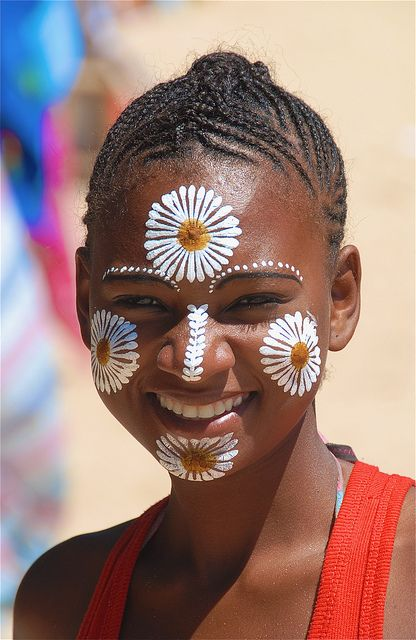 gorgeous indonesian woman wearing painted flowers african facepaint