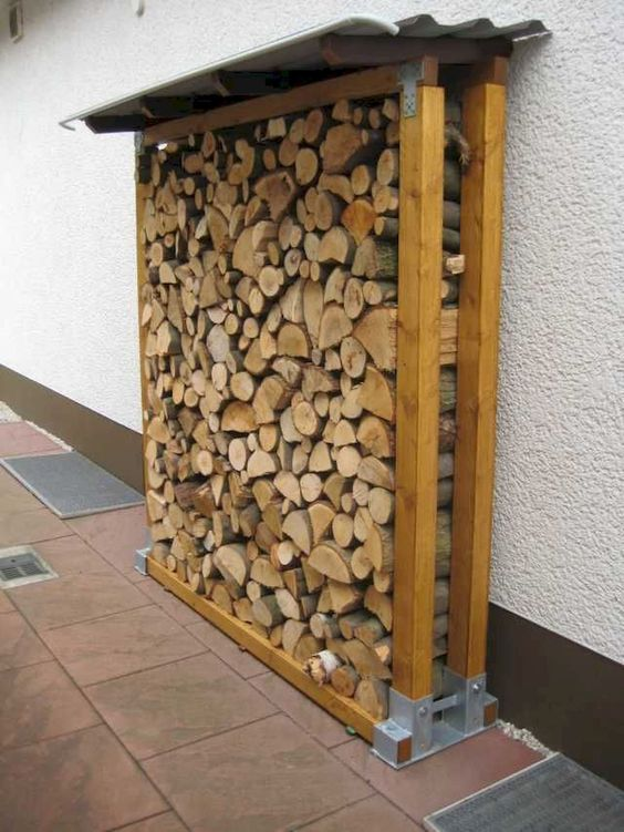 firewood rack sits against a wall #fireWoodStorage #firewoodrack #firewood #firewoodideas #organization #shed
