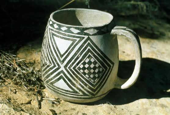 This mug, made in the 13th century (A.D. 1200s), represents the exceptional artistic expression of the Ancestral Puebloan people.  Mesa Verde pottery typically featured black geometric patterns applied with a yucca paintbrush on a grayish white background.  These patterns were remarkable for their balance and design.: