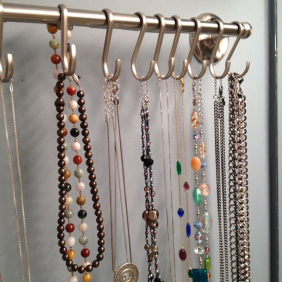 Necklace holder made from a towel rack and shower curtain hooks.