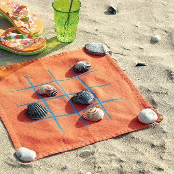 Serviette peinte de rayures pour faire un jeu de morpion et jouer sur la plage avec des coquillages