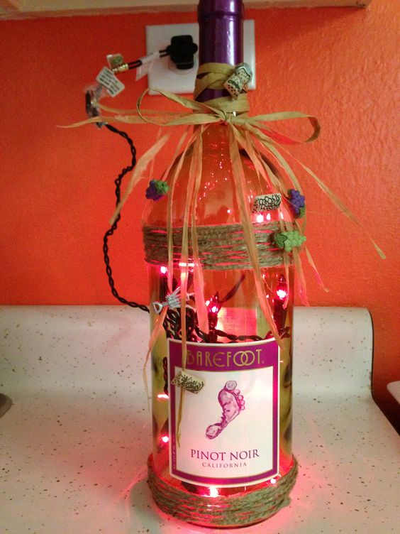 Drink wine! Drill a hole, add lights, double sided tape where jute can look nice. Raffia bow and tear edges!