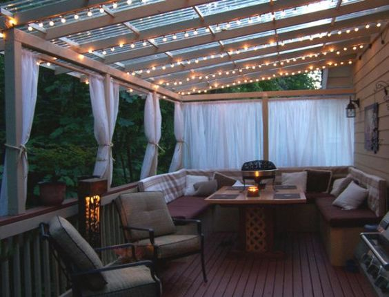 Gorgeous backyard deck. Love the curtains and lights.