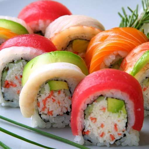 Rainbow Roll • An assortment of fish and avocado on top of a California Roll. More