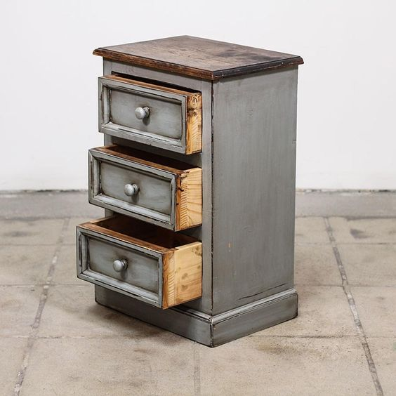 This shabby chic nightstand is featured in a solid wood with a distressed light blue gray paint finish. This rustic farmhouse end table is in great condition with 3 drawers, carved trim and a raw wood table top. Rustic bed side table perfect for a warm space!·Material: Wood   ·Dimensions: 18x12.75x27.75   ·Condition: Very good   ·Number_of_pieces: 1   Available now on Loveseat.