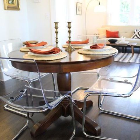 A Vintage Rustic Round Table Plus Clear Acrylic Chairs For A Cozy