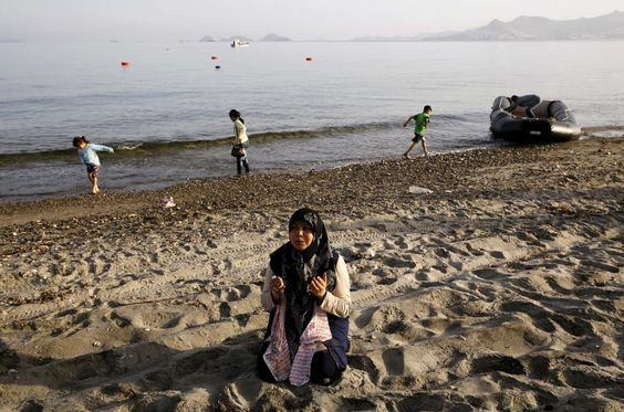 A Syrian refugee woman cries as she prays on the beach after arriving on Kos with her family on a dinghy boat, early May 26, 2015. REUTERS/Yannis Behrakis
