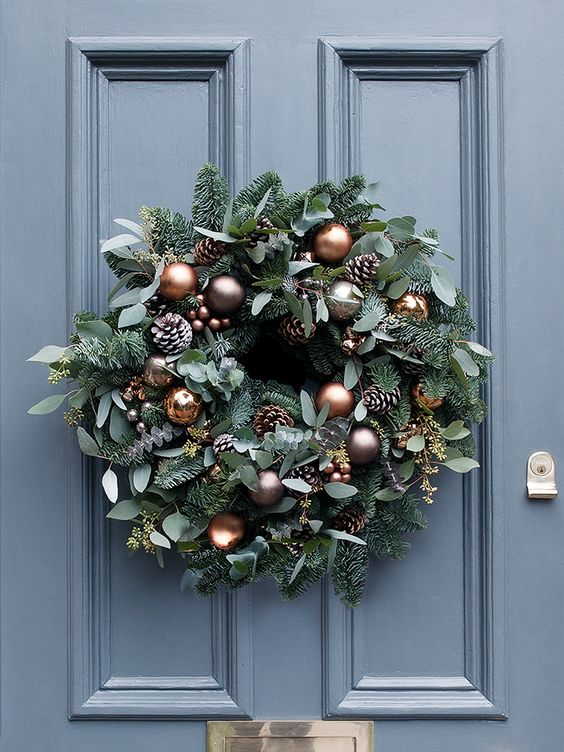A sumptuous array of seasonal foliage, beautiful copper and mink baubles, frosted pine cones and miniature copper bells. The perfect centrepiece for your front door.: