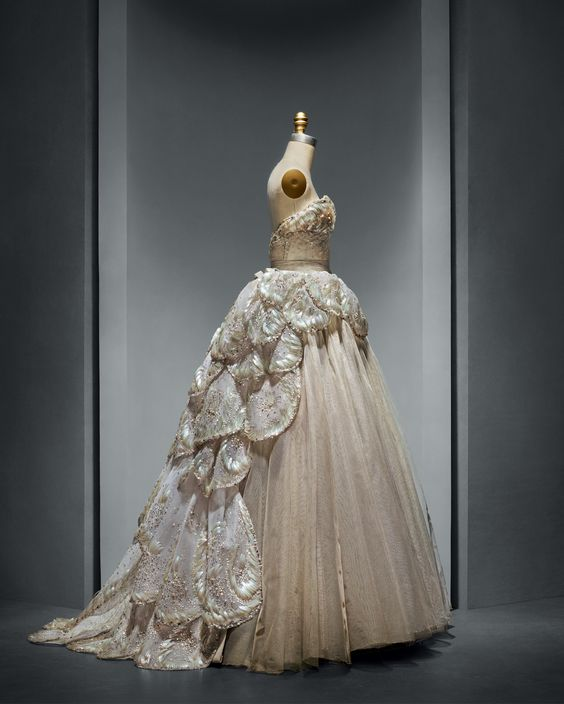 """House of Dior (French, founded 1947), Christian Dior (French, 1905–1957). """"Venus"""" Dress, autumn/winter 1949–50, Haute Couture. Machine–sewn, hand–finished gray silk taffeta and tulle; hand–applique of gray silk tulle and horsehair petals, hand–embroidered with opalescent, gold, and silver gelatin sequins, feather paillettes, synthetic pearls, and clear crystals. Photo © Nicholas Alan Cope. #ManusxMachina #CostumeInstitute"""