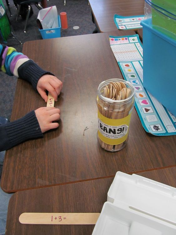 Math Fact BANG! Kids pull a stick, read the fact, answer correctly and they keep the stick.  If they pull out a BANG they have to put all their sticks back.