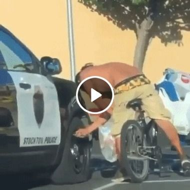 Cara seca o pneu do carro da policia em rua