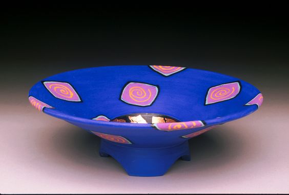 """Small bowl shown in blue.  Clay. Approximate size is 10"""" dia  3"""" h. Layered matte glazes with goldish or copper leaf in center.  Other colors: orange, coral, light blue, lavender, teal green, tobacco brown, purple.  Not food safe.  $65."""