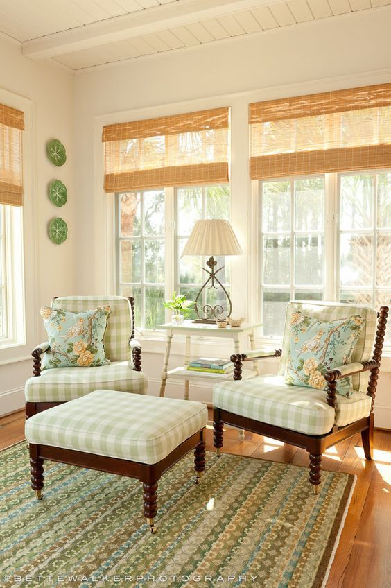 Interior design ideas and Spring decor inspiration! A stunning sunroom decorated with green, spindle style arm chairs, natural woven blinds, and Buffalo checks.
