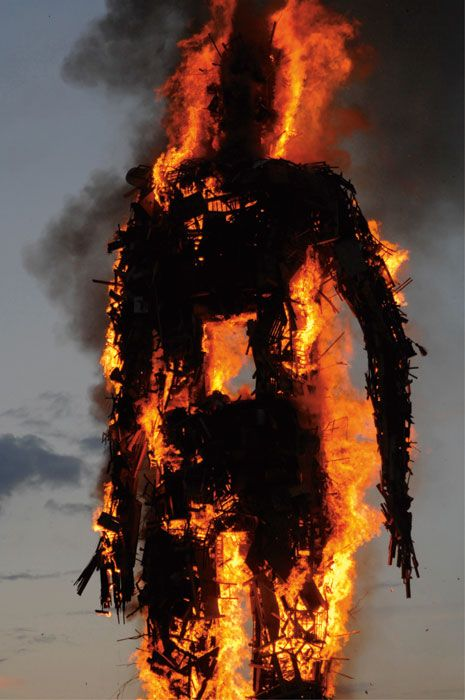 Anthony Gormley - Waste Man. 'Sticking it to the man!' This is a great angle to show the colossal size of the burning statue.