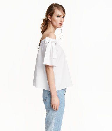 Weiß. Weite, schulterfreie Bluse aus weicher, luftiger Baumwolle. Die Bluse hat oben einen Gummizug und kurze Ärmel mit breiten Bindebändern.