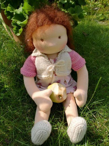 """Super süßes Puppenmädchen mit """"beröseltem"""" Kleidchen, Strickbolero und Häkelschühchen. Ihr rotbraunes Haar hat sie mit rosa Schleifen zu zwei kleinen"""
