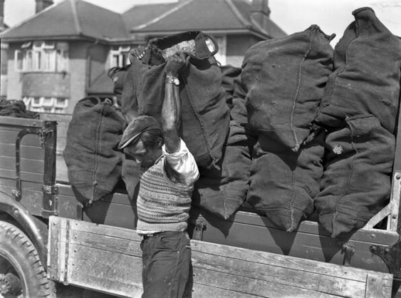 Coal man delivering coal. Most people had coal bunkers in their back gardens where the coal man emptied the sacks of coal.