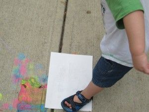 Sidewalk paint, use foot to make a print. Try in the shade outside next summer.