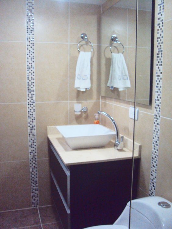 Mueble de baño color makana, meson marmol crema claro.