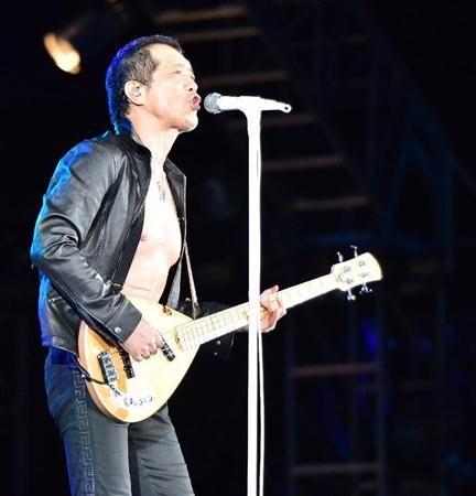 素肌に黒いジャケットを着て歌っている矢沢永吉の画像