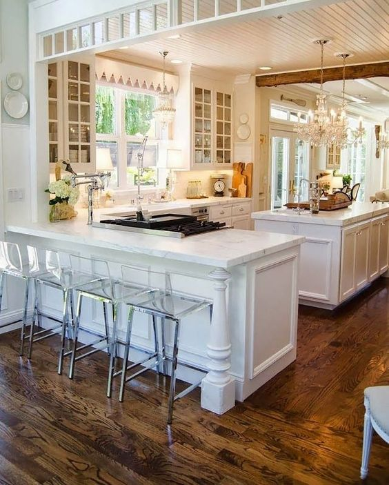 Beautiful, spacious white kitchen with contrasting wood flooring.