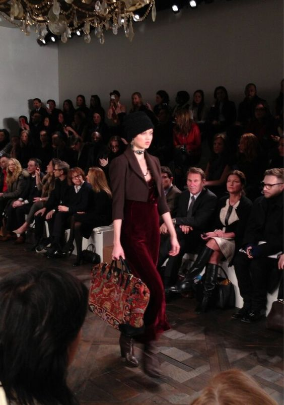 Robe longue en velours rouge sous un boléro couleur taupe et sac à motif tapisserie au défilé #RalphLauren