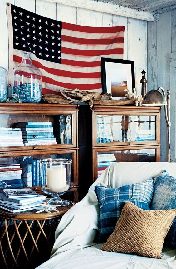 Casual, coastal, Americana interior design inspiration from Ralph Lauren Home. A relaxed coastal cottage style feel in a country room with red, white, and blue and the American flag hung above barrister bookcases. #traditionaldecor #casual #coastal #interiordesign #ralphlauren #redwhiteblue #americanflag #americana