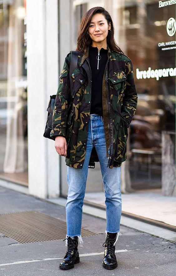 Look com jeans, moletom, parka camuflada e coturno.
