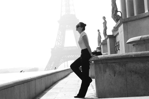 Fashion blogger Andy Torres from StyleScrapbook at the Eiffel Tower in Paris wearing wide legged pants and Celine sunglasses