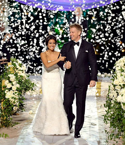 Sean Lowe and Catherine Giudice from the Bachelor Season 17 walk down the aisle under rose petal confetti with draped floral arrangements as aisle decor.
