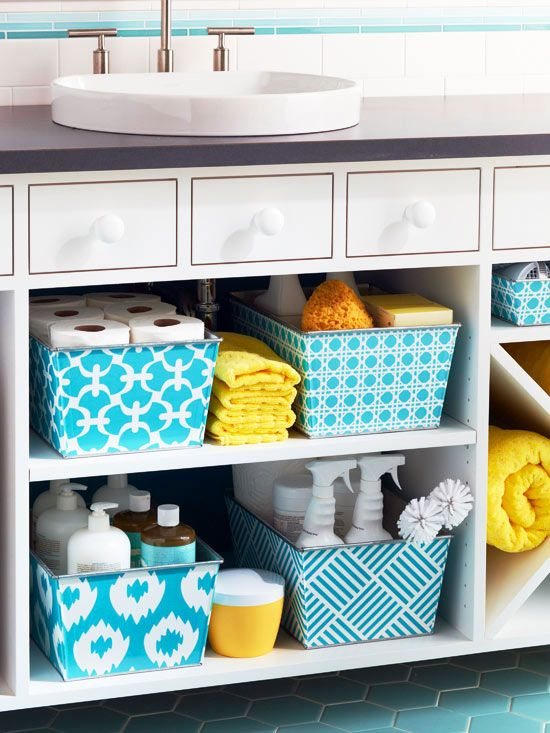 """Cleaning Supply Storage on Display  """"When a linen closet isn't an option, a spacious open vanity is the perfect place for household extras. Decorative storage bins fill the shelves of this open vanity to create a cleaning catchall that's both stylish and functional. Separate your cleaning supplies by use and neatly arrange them in bins to prevent your bathroom from looking cluttered and messy."""""""