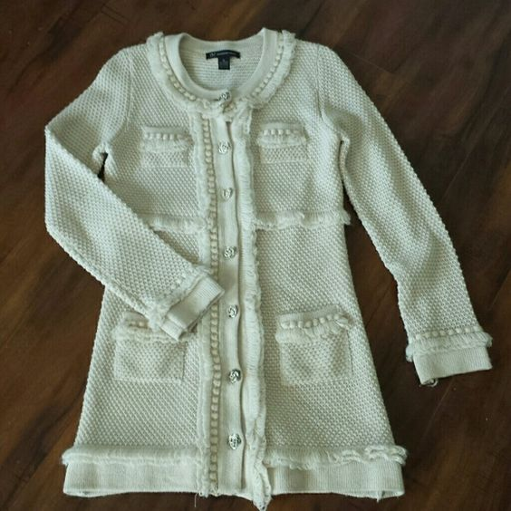 INC sweater 70% acrylic,  30% wool. Cream colored fringe with gold accents on the trim and silver toned buttons with rhinestone accents. The knitted wool structure offers a soft, warm fit. INC International Concepts Sweaters Cardigans