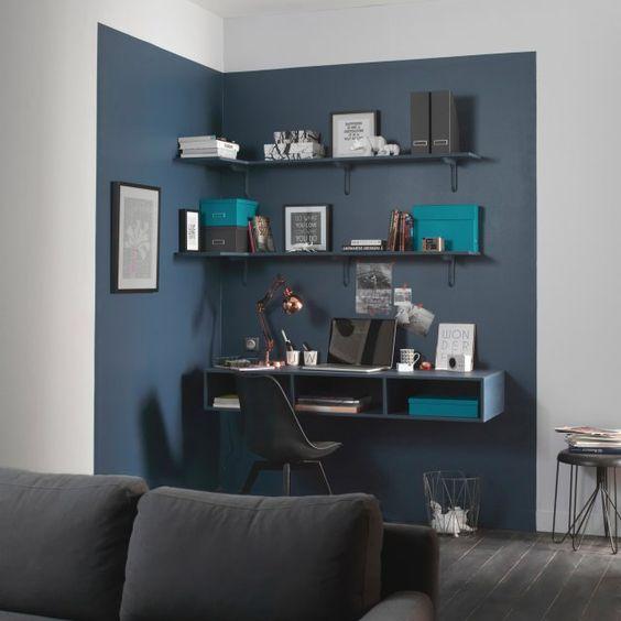 Une délimitation colorée au mur pour un max d'effet. Dans ce salon épuré, l'espace bureau est délimité par un bleu marine masculin et intense. Une démarcation visuelle au mur qui sépare de manière distincte le coin bureau du reste de la pièce, pour un coin bureau design et gain de place.: