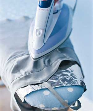 To get wrinkles out of silk, wool, and rayon clothes that can't take direct heat, place a piece of foil on your ironing board, then lay the garment flat over it. With the steam button down, pass the iron three to four inches over the fabric several times. Wet heat radiating from the foil helps smooth out wrinkles.