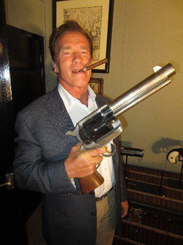Arnold Schwarzenegger smoking a cigar, holding a massive pistol.