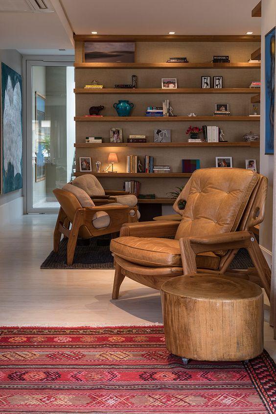 Decoração de apartamento para viver e receber. Prateleira de madeira com livros e adornos, poltrona de madeira, sofá, mesa de centro de madeira com plantas.     #decoracao #decor #details #casadevalentina