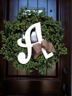 Wreath with wooden letter and tied with burlap bow. Easy.